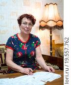 Пожилая женщина просматривает квитанции за коммунальные услуги. Стоковое фото, фотограф Вячеслав Палес / Фотобанк Лори