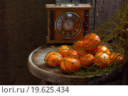 Мандарины в сетке-авоське и старые часы на деревянном столе. Стоковое фото, фотограф Марина Володько / Фотобанк Лори