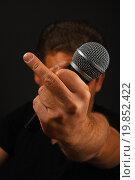 Купить «Мужская рука с микрофоном, жест fuck off», фото № 19852422, снято 16 декабря 2015 г. (c) Anton Eine / Фотобанк Лори