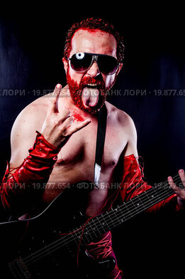 guitarist with electric guitar black, wearing face paint and red leather