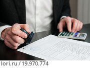 Купить «Мужчина с калькулятором и печатью работает с документами», эксклюзивное фото № 19970774, снято 10 января 2016 г. (c) Игорь Низов / Фотобанк Лори