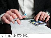 Купить «Бизнесмен с калькулятором работает с документами», эксклюзивное фото № 19970802, снято 10 января 2016 г. (c) Игорь Низов / Фотобанк Лори