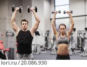 Купить «smiling man and woman with dumbbells in gym», фото № 20086930, снято 30 ноября 2014 г. (c) Syda Productions / Фотобанк Лори