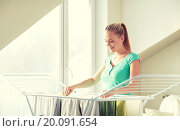Купить «happy woman hanging clothes on dryer at home», фото № 20091654, снято 25 января 2015 г. (c) Syda Productions / Фотобанк Лори