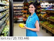 Купить «Portrait of a smiling woman doing shopping», фото № 20193446, снято 14 апреля 2015 г. (c) Wavebreak Media / Фотобанк Лори