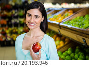 Купить «Portrait of a smiling woman picking apple», фото № 20193946, снято 14 апреля 2015 г. (c) Wavebreak Media / Фотобанк Лори