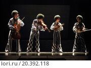 Купить «MOSCOW - MAR 12, 2014: Four actors Taper-show: dancing on the strings in black wigs and costumes with musical instruments on stage of the Palace on Yauza», фото № 20392118, снято 12 марта 2014 г. (c) Losevsky Pavel / Фотобанк Лори