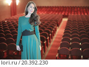 Купить «Beautiful young woman with dark long hair in a green evening dress standing in an empty auditorium», фото № 20392230, снято 12 марта 2014 г. (c) Losevsky Pavel / Фотобанк Лори