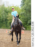 Купить «Young boy in blue shirt riding a horse in park near the apartment complex», фото № 20392638, снято 14 августа 2014 г. (c) Losevsky Pavel / Фотобанк Лори