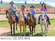cowboy family of four on horses on background of paddock, фото № 20393454, снято 29 июня 2014 г. (c) Losevsky Pavel / Фотобанк Лори
