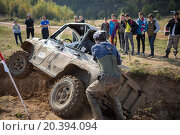 Купить «RUSSIA, PUSHKINO – 20 SEP, 2014: Rally team member is helping to pull off-road vehicle at Rainforest Challenge Russia Autumn 2014 PRO-X.», фото № 20394094, снято 20 сентября 2014 г. (c) Losevsky Pavel / Фотобанк Лори