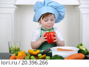 Купить «Little girl in kitchen apron and cap with large red pepper», фото № 20396266, снято 1 апреля 2014 г. (c) Losevsky Pavel / Фотобанк Лори