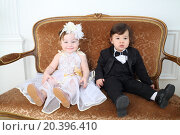Купить «Beautiful little kids in costumes bride and groom sitting on couch», фото № 20396410, снято 1 апреля 2014 г. (c) Losevsky Pavel / Фотобанк Лори