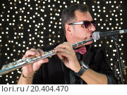 Купить «Musician with flute in a bow tie playing in a club with garlands», фото № 20404470, снято 2 апреля 2014 г. (c) Losevsky Pavel / Фотобанк Лори