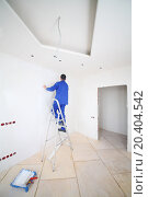 Купить «Back of worker in blue on ladder pasting paint fiberglass in new apartment», фото № 20404542, снято 11 декабря 2013 г. (c) Losevsky Pavel / Фотобанк Лори