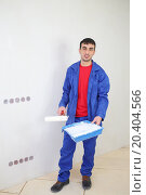 Купить «Happy worker in blue clothes stands with paint roller in new apartment», фото № 20404566, снято 11 декабря 2013 г. (c) Losevsky Pavel / Фотобанк Лори