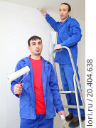 Купить «Happy workers in blue clothes hold construction tools and stand on ladder in new apartment», фото № 20404638, снято 11 декабря 2013 г. (c) Losevsky Pavel / Фотобанк Лори