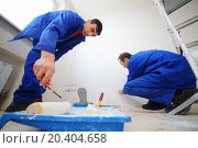 Купить «Workers in blue glue paint fiberglass and paint walls in new apartment», фото № 20404658, снято 11 декабря 2013 г. (c) Losevsky Pavel / Фотобанк Лори