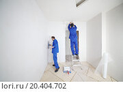 Купить «Skillful workers in blue glue paint fiberglass on ladder in new apartment», фото № 20404702, снято 11 декабря 2013 г. (c) Losevsky Pavel / Фотобанк Лори