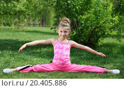 Купить «Little girl in pink performs exercise splitting legs apart on grass at day outdoors.», фото № 20405886, снято 13 мая 2013 г. (c) Losevsky Pavel / Фотобанк Лори