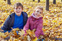 Laughing boy and girl sit on ground in drift of yellow fallen maple leaves in autumn park, фото № 20406294, снято 13 октября 2013 г. (c) Losevsky Pavel / Фотобанк Лори