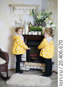 Купить «Two little girls in same clothes stands near fireplace and wicker rocking chair and warm hands in cosy room.», фото № 20406670, снято 20 октября 2013 г. (c) Losevsky Pavel / Фотобанк Лори