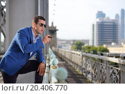 Купить «Handsome man in blue jacket and sunglasses with cigar stands on bridge and looks away.», фото № 20406770, снято 19 июля 2013 г. (c) Losevsky Pavel / Фотобанк Лори
