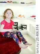 Купить «Little pretty girl sits on big pouf and holds sandal in children store.», фото № 20406814, снято 18 мая 2013 г. (c) Losevsky Pavel / Фотобанк Лори