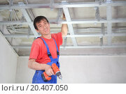 Купить «Smiling worker is installing a ceiling profile for false ceiling», фото № 20407050, снято 20 июля 2013 г. (c) Losevsky Pavel / Фотобанк Лори