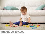 Купить «Barefoot baby sits on carpet and plays with wooden cubes near sofa. Shallow depth of field.», фото № 20407090, снято 23 октября 2013 г. (c) Losevsky Pavel / Фотобанк Лори