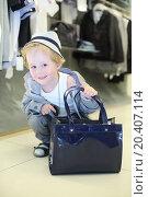 Купить «Little boy with bag sits near clothes hangers in children clothing shop.», фото № 20407114, снято 18 мая 2013 г. (c) Losevsky Pavel / Фотобанк Лори