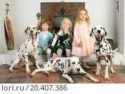 Купить «Two boys and girl in medieval costumes rest near fireplace with hanging pot with dalmatians.», фото № 20407386, снято 2 ноября 2013 г. (c) Losevsky Pavel / Фотобанк Лори