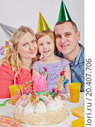 Купить «Mother, father and little daughter sit cheek to cheek at birthday table», фото № 20407706, снято 7 ноября 2013 г. (c) Losevsky Pavel / Фотобанк Лори