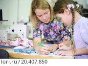 Купить «Female tailor teaches student girl use of templates near sewing machine. Focus on girl.», фото № 20407850, снято 27 апреля 2013 г. (c) Losevsky Pavel / Фотобанк Лори