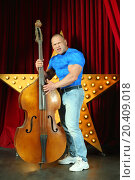 Купить «Strong man with big muscles in blue t-shirt playing on stage with contrabass», фото № 20409018, снято 19 апреля 2014 г. (c) Losevsky Pavel / Фотобанк Лори