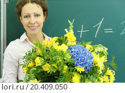 Купить «Happy teacher with big bunch of flowers stands near chalkboard in classroom at school.», фото № 20409050, снято 17 августа 2013 г. (c) Losevsky Pavel / Фотобанк Лори