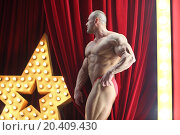 Strong man with big muscles standing on red stage with big lights star. Стоковое фото, фотограф Losevsky Pavel / Фотобанк Лори