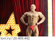 Strong man with big muscles shows his physique on red stage with big lights star. Стоковое фото, фотограф Losevsky Pavel / Фотобанк Лори