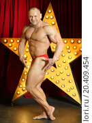 Strong man with big muscles demonstrates his physique on stage with big lights star. Стоковое фото, фотограф Losevsky Pavel / Фотобанк Лори