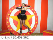 Купить «Circus actress in a black ballet tutu stands on circular disc with star», фото № 20409562, снято 19 апреля 2014 г. (c) Losevsky Pavel / Фотобанк Лори