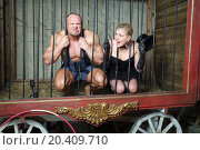 Athlete and actress sit on their knees behind bars in cage for animals. Стоковое фото, фотограф Losevsky Pavel / Фотобанк Лори