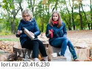 Купить «Женщина и девушка сидят на пеньках с термосами на природе», эксклюзивное фото № 20416230, снято 1 октября 2015 г. (c) Игорь Низов / Фотобанк Лори