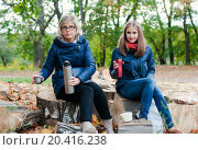 Купить «Женщина и девушка сидят на пеньках с термосами», эксклюзивное фото № 20416238, снято 1 октября 2015 г. (c) Игорь Низов / Фотобанк Лори