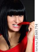 Купить «Девушка кусает острый перец», фото № 20669714, снято 1 декабря 2012 г. (c) Арестов Андрей Павлович / Фотобанк Лори