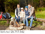 Купить «happy family sitting on bench at camp fire», фото № 20717542, снято 27 сентября 2015 г. (c) Syda Productions / Фотобанк Лори