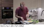 Купить «Человек на кухне готовит рыбу», видеоролик № 20721842, снято 7 января 2016 г. (c) Валентин Беспалов / Фотобанк Лори