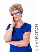 Купить «Улыбающаяся пожилая женщина в синем платье и в очках с синей оправой, белый фон», фото № 20727726, снято 13 декабря 2015 г. (c) Кекяляйнен Андрей / Фотобанк Лори