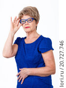 Купить «Женщина в возрасте поправляет свои очки рукой, белый фон», фото № 20727746, снято 13 декабря 2015 г. (c) Кекяляйнен Андрей / Фотобанк Лори