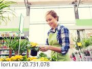 Купить «happy woman holding flowers in greenhouse», фото № 20731078, снято 25 февраля 2015 г. (c) Syda Productions / Фотобанк Лори