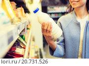 Купить «happy woman holding milk bottle in market», фото № 20731526, снято 20 декабря 2014 г. (c) Syda Productions / Фотобанк Лори